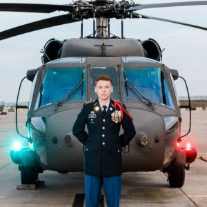 Premium senior portrait photography session of an Austin, TX high school senior JROTC boy and future U.S. Coast Guardsman poses in the sunset next to a Blackhawk helicopter at a U.S. Army base.