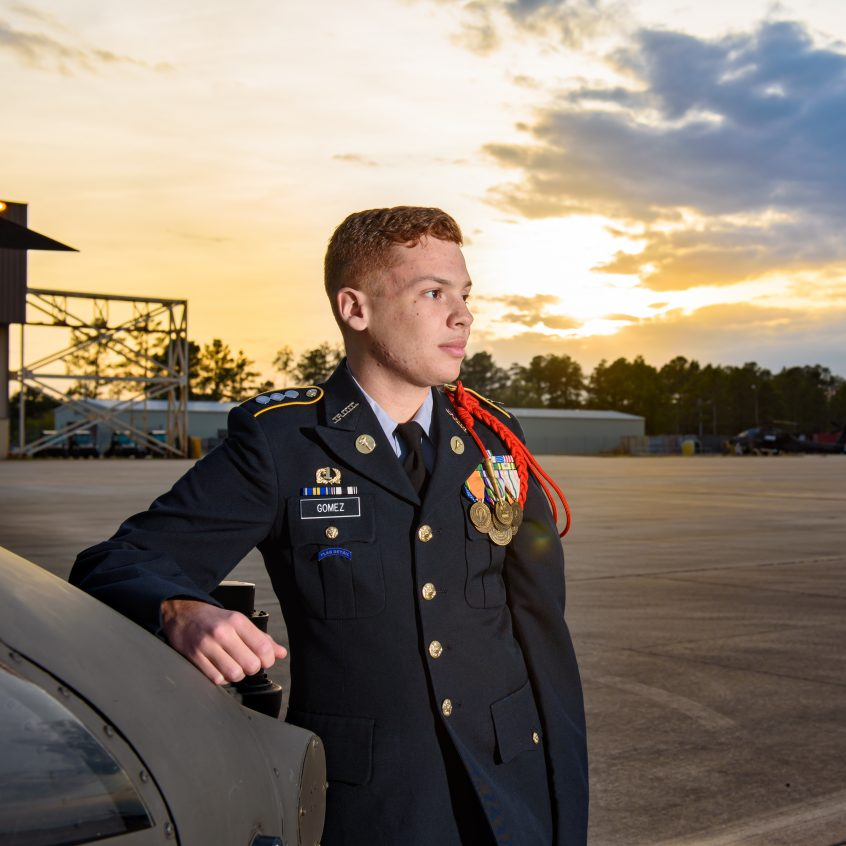 High school senior JROTC boy and future U.S. Coast Guardsman poses in the sunset next to a Blackhawk helicopter at a U.S. Army base.
